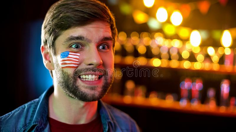 Emotional man with american flag on cheek smiling watching sport match in bar stock image