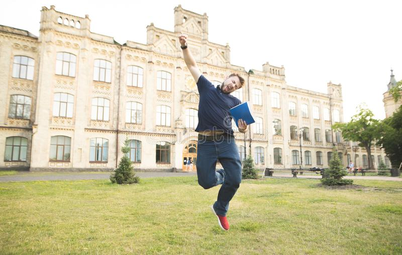 Emotional man with books in his hands jumping with joy. The student passed the exam. Happy student with books in his hands jumps on campus at the background of stock photos