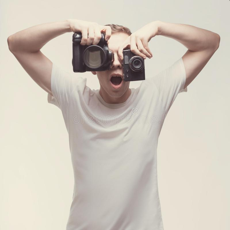 Emotional Man with camera isolated on light background. Young man hold digital camera and old tape camera. Lifestyle, travel and stock photos