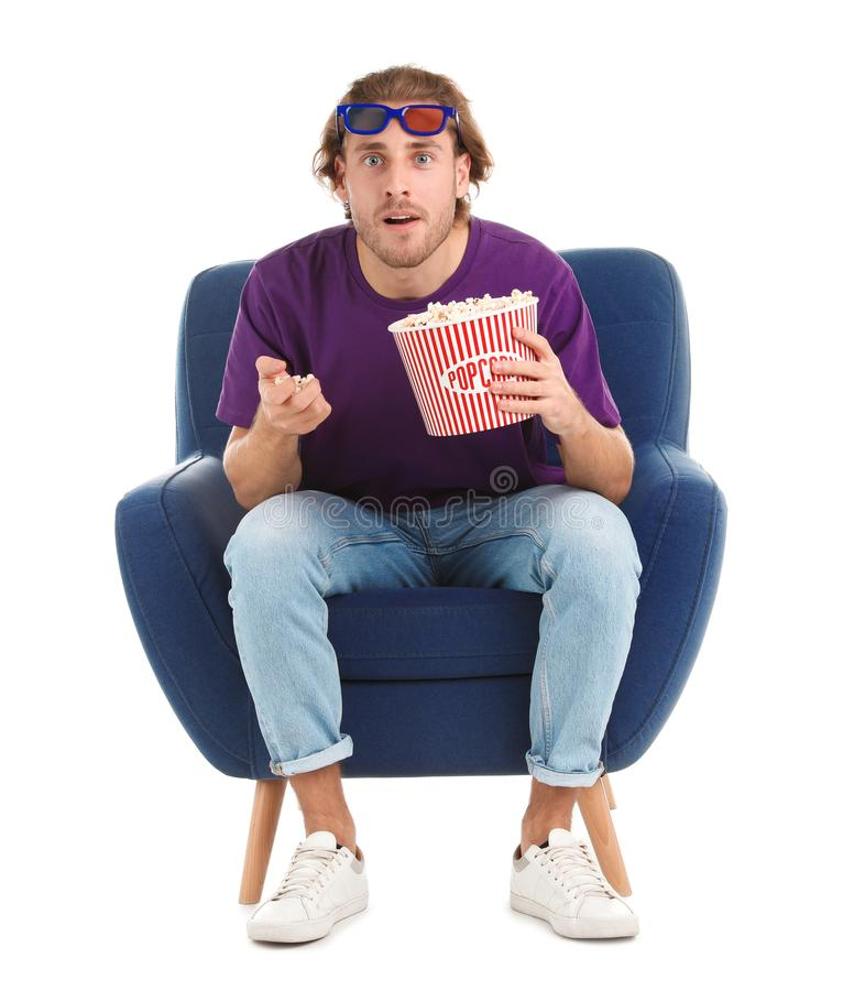 Emotional man with 3D glasses and popcorn sitting in armchair during cinema show on white royalty free stock photos