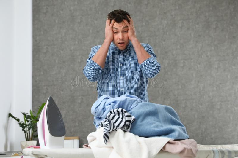 Emotional man near board with iron and pile of clothes. At home royalty free stock photography