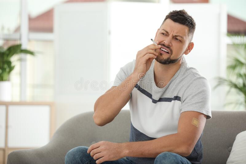 Emotional man with nicotine patch and cigarette stock photography