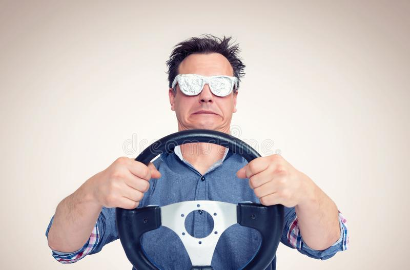 Emotional man in opaque aluminum glasses with steering wheel. Front view. Car driver concept royalty free stock photos