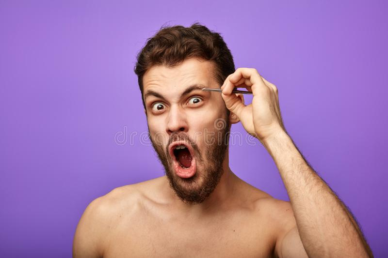 Emotional man plucks his eyebrows with tweezers. Emotional man with wide open mouth plucks his eyebrows with tweezers in the morning. skin, face care, beauty stock photos