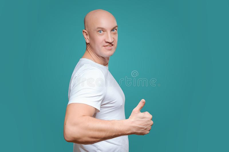 An emotional man in a white t-shirt shows with a hand gesture that everything is cool, on a Titian background stock photography