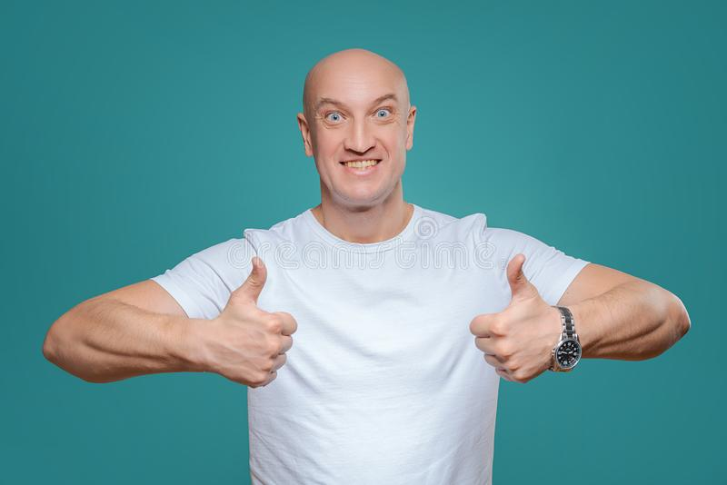 An emotional man in a white t-shirt shows with a hand gesture that everything is cool, on a Titian background royalty free stock photo