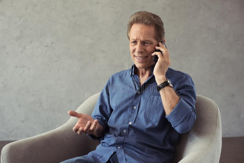 emotional mature man talking on smartphone while sitting stock image