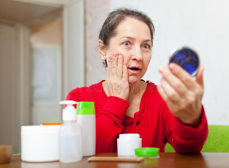 Emotional mature woman stares on face. Emotional mature woman stares on her face in mirror at home royalty free stock photo