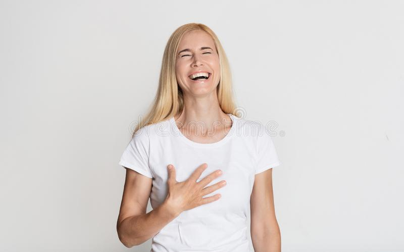 Emotional middle-aged woman laughing and touching her chest royalty free stock images