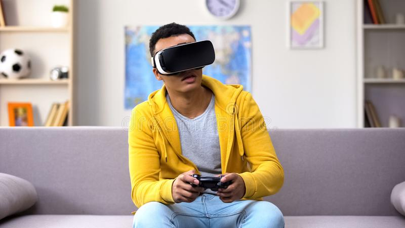 Emotional mixed-race guy in VR headset playing video game, reality simulation. Stock photo royalty free stock image