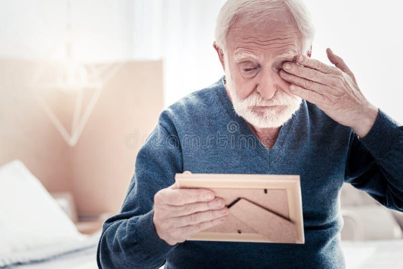Sad elderly man wiping away tears royalty free stock photo