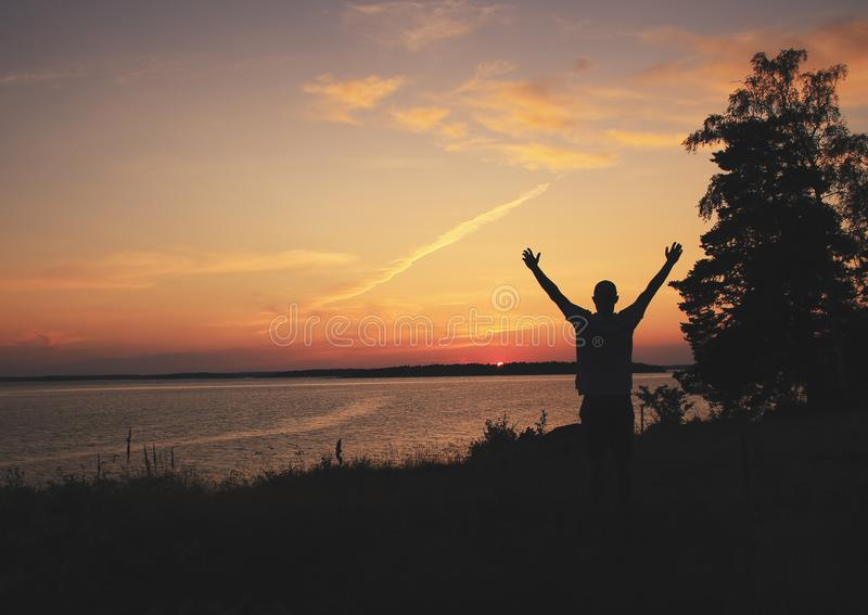 Emotional moments. Person raising arms at a sunrise / sunset with beautiful colors and marine environment. Holiday theme. Emotional moments. Person raising arms stock images