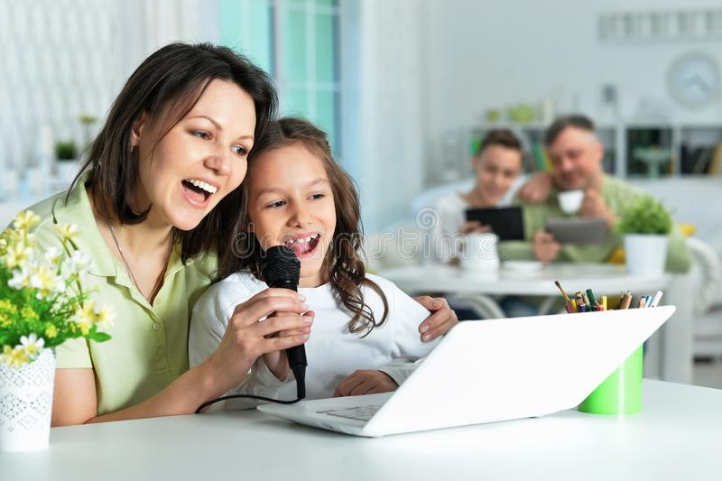 Portrait of emotional mother and daughter singing karaoke with laptop at home stock photo