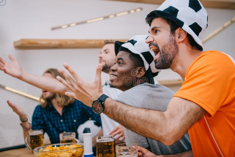 emotional multicultural group of male football fans gesturing by hands and watching soccer match stock images