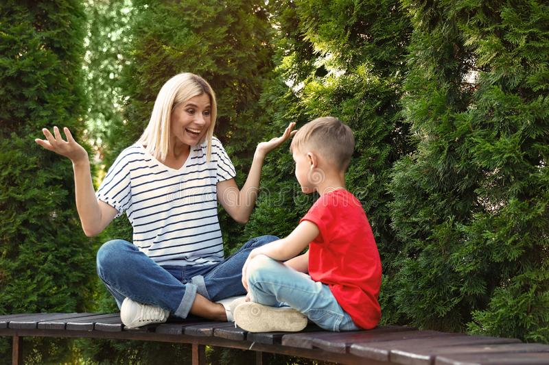 Emotional nanny with cute little boy on bench royalty free stock photo