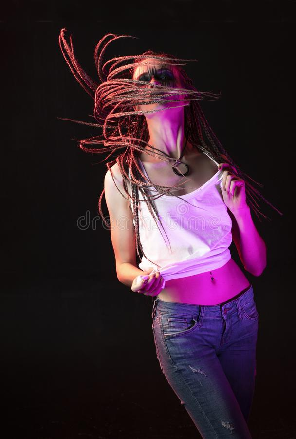 Emotional photo of a beautiful slim girl with creative make-up and a hairstyle of cornrows, wearing white t-shirt, dancing waves royalty free stock photo