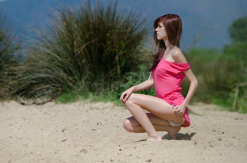 Emotional picture of a cute lady near a lake. Emotional picture of a cute red hair lady near a lake, wearing jean shorts and a shirt, sitting on legs in sideways stock images
