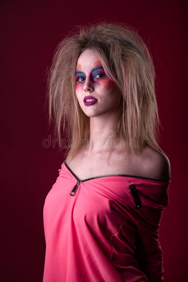 Attractive young girl with disheveled hair. Emotional Portrait of a Attractive young girl with carnival colorful makeup and disheveled hair royalty free stock photography