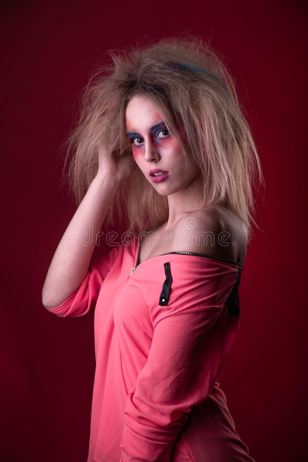Attractive young girl with disheveled hair. Emotional Portrait of a Attractive young girl with carnival colorful makeup and disheveled hair royalty free stock photo