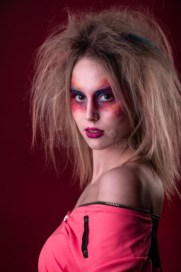 Attractive young girl with disheveled hair. Emotional Portrait of a Attractive young girl with carnival colorful makeup and disheveled hair stock images
