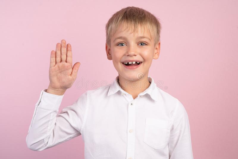 Emotional portrait of caucasian smiling litlle boy wearing white shirt, stretching his right hand up for greeting. Happy child stock photo