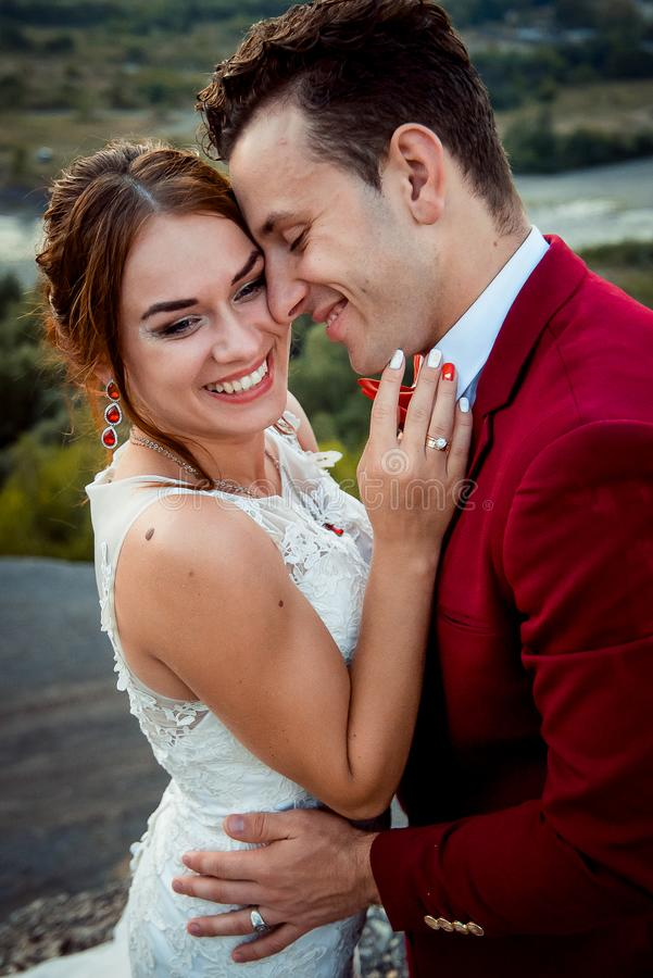 Emotional portrait of the cheerful newlyweds smiling and hugging outdoor. stock photo