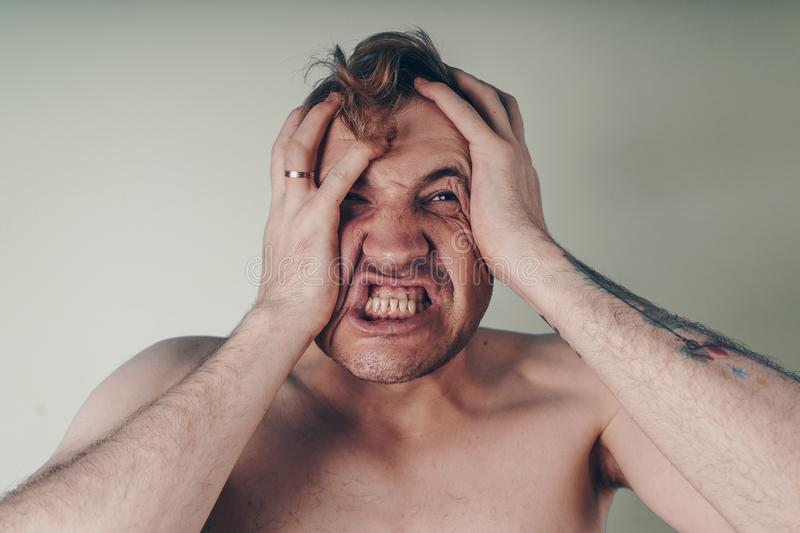 Emotional portrait of a crazy guy in close-up. concept: the nervous breakdown, mental disease, headaches and migraine. black and w. Emotional portrait of a crazy royalty free stock photo