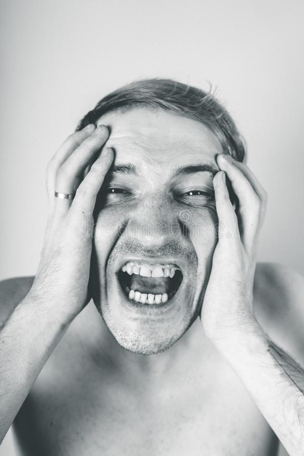 Emotional portrait of a crazy guy in close-up. concept: the nervous breakdown, mental disease, headaches and migraine. black and w. Emotional portrait of a crazy royalty free stock image