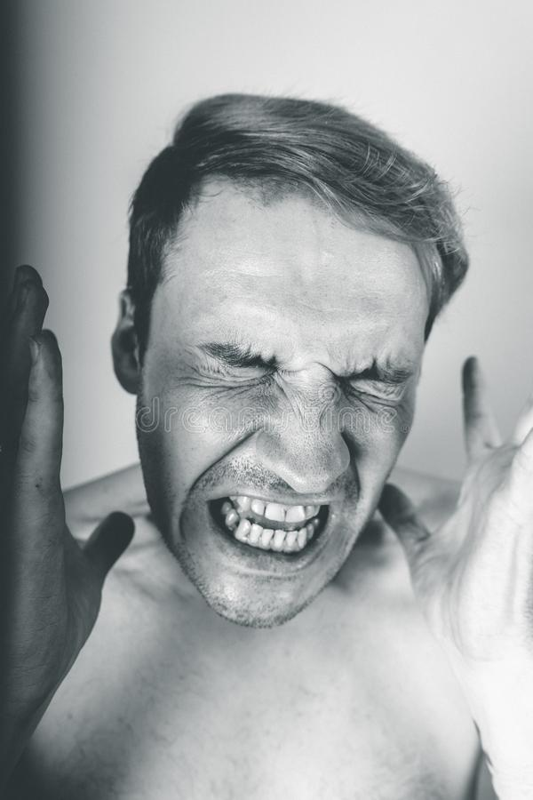 Emotional portrait of a crazy guy in close-up. concept: the nervous breakdown, mental disease, headaches and migraine. black and w. Emotional portrait of a crazy stock images