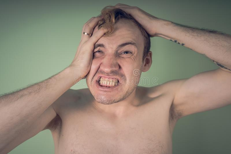Emotional portrait of a crazy guy in close-up. concept: the nervous breakdown, mental disease, headaches and migraine.  royalty free stock image