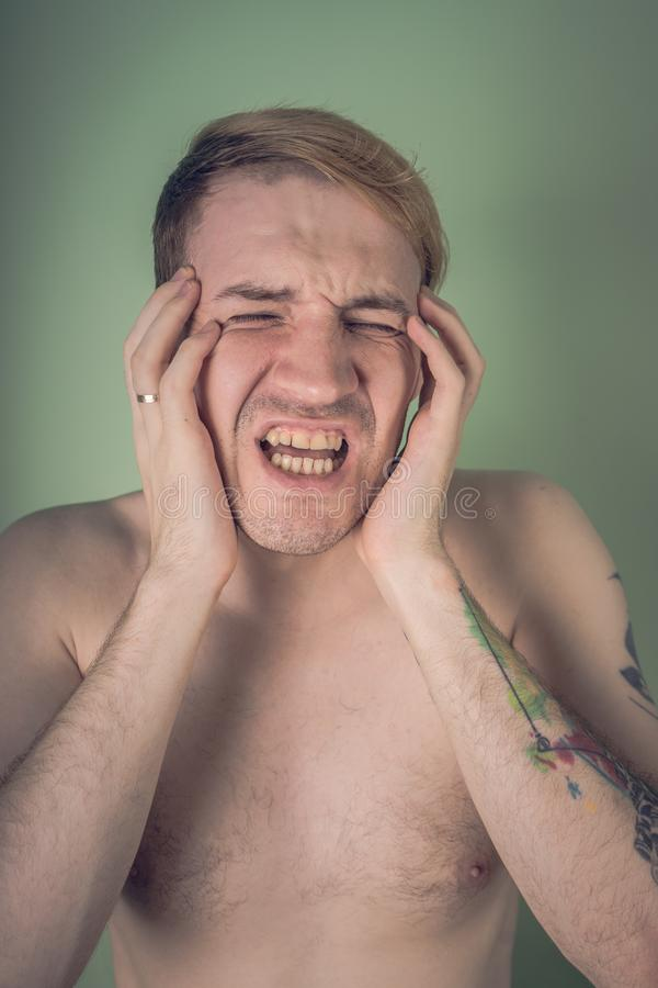 Emotional portrait of a crazy guy in close-up. concept: the nervous breakdown, mental disease, headaches and migraine.  stock image