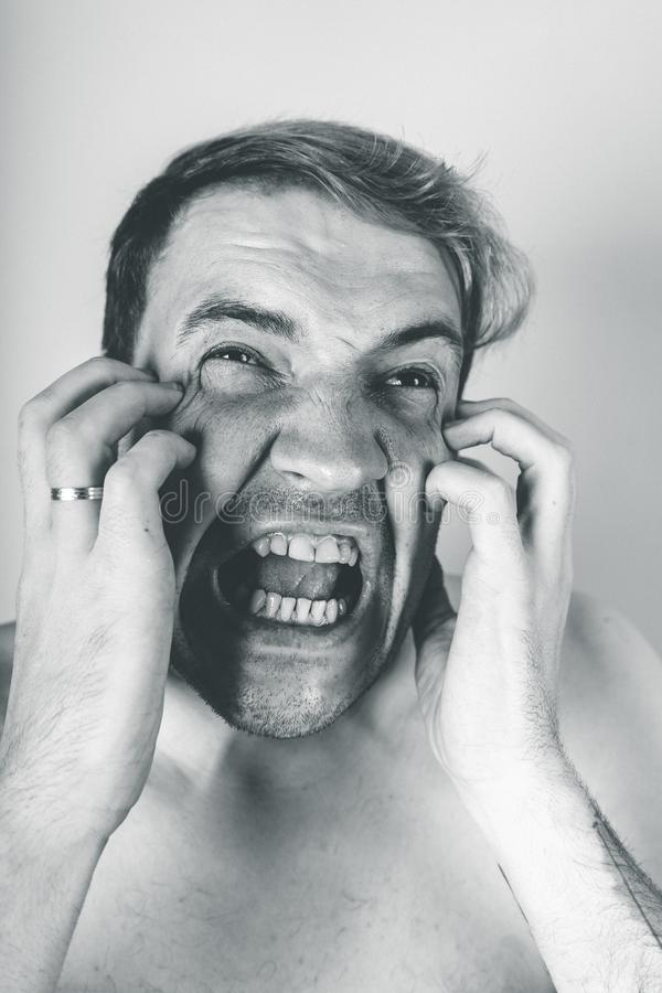 Emotional portrait of a crazy guy in close-up. concept: the nervous breakdown, mental disease, headaches and migraine. black and w. Emotional portrait of a crazy royalty free stock photography