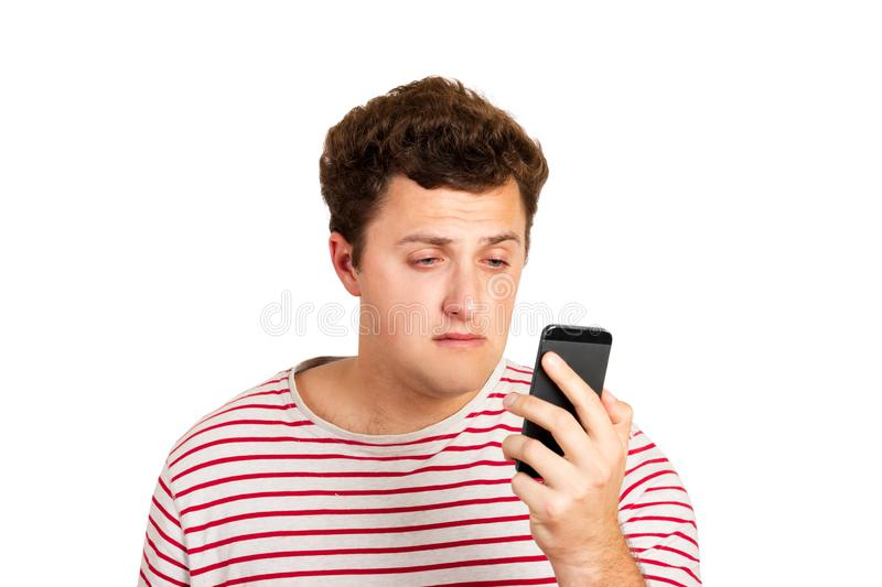 Emotional portrait of a crying man looking at his mobile phone. feeling of hopelessness. emotional man isolated on white backgroun royalty free stock photography