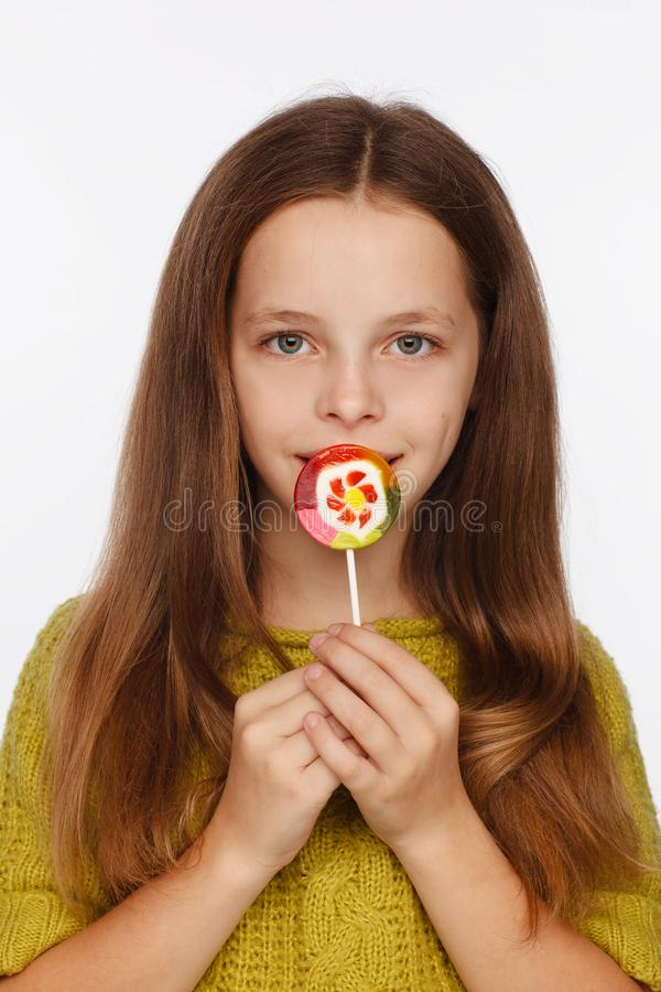 Emotional portrait of an eight-year girl in a yellow-green sweater and with a lollipop in her hands royalty free stock photography