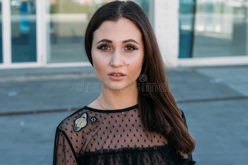 Emotional portrait of Fashion stylish portrait of pretty young woman. city portrait. sad girl. brunette in a black dress royalty free stock photo