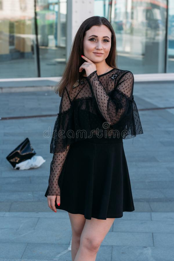Emotional portrait of Fashion stylish portrait of pretty young woman. city portrait. sad girl. brunette in a black dress. expectat stock photography