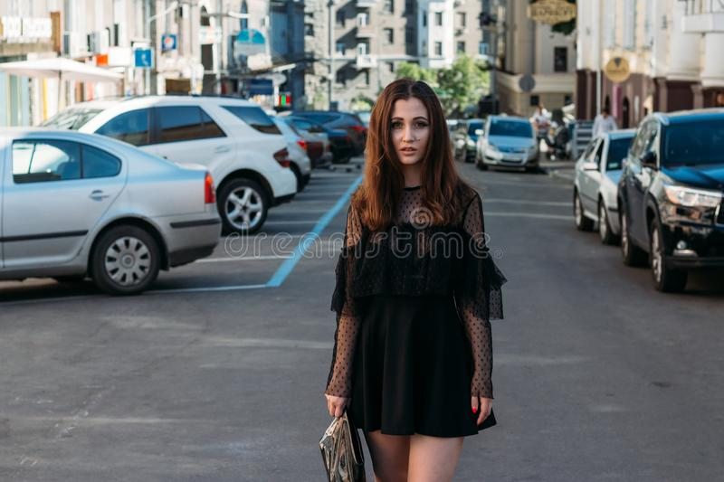 Emotional portrait of Fashion stylish portrait of pretty young woman. city portrait. sad girl. brunette in a black dress. expectat royalty free stock images