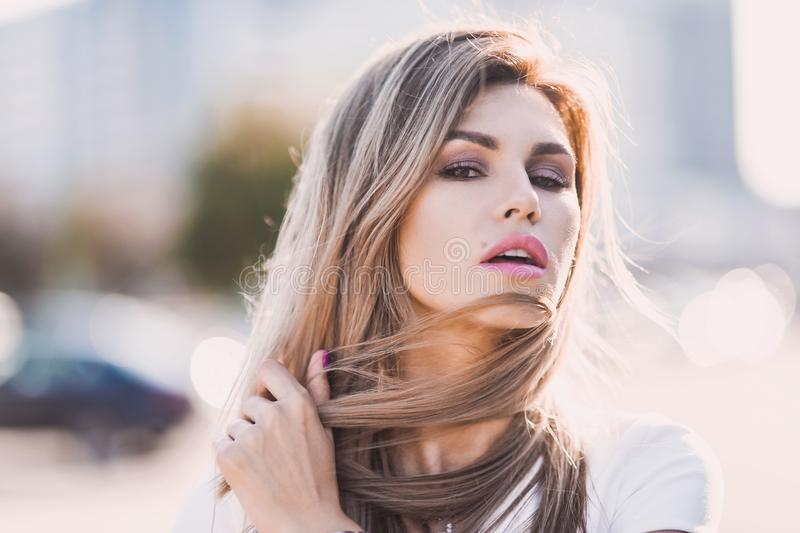 Portrait of Fashion stylish of young hipster blonde woman, elegant lady, bright colors dress, cool girl. City view urban l royalty free stock photo