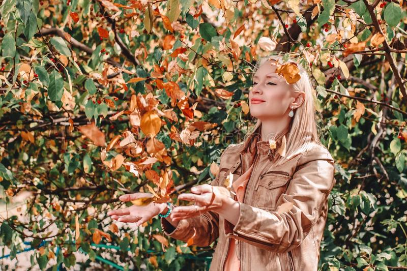 Emotional portrait of a happy and cheerful blonde woman in a leather jacket, with a smile throwing yellow maple leaves up in the stock image