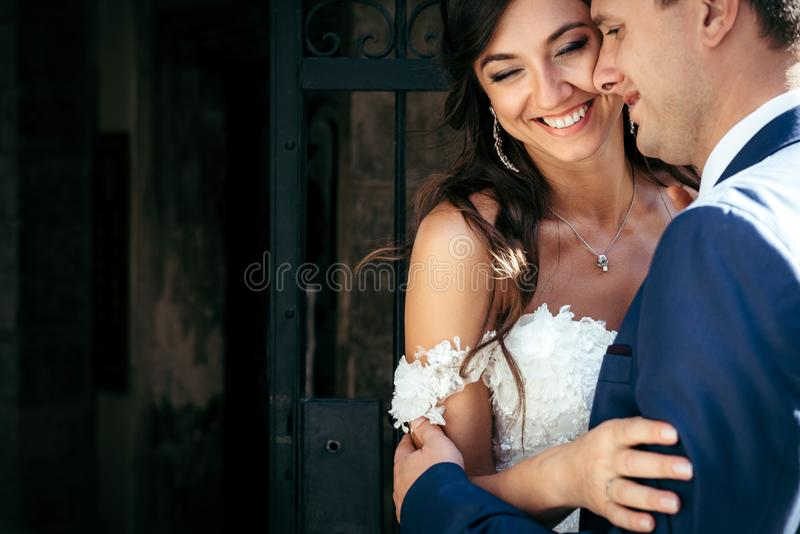 Emotional portrait of the happy hugging newlyweds. Outdoor location. royalty free stock images