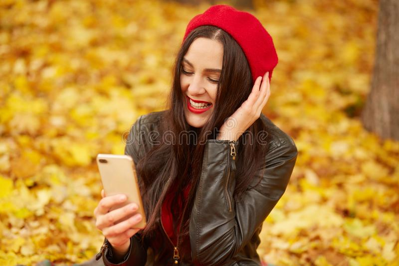 Emotional portrait of happy and relaxed beautiful young woman with dark hair, dresses beret and jacket, looks smiling at phone royalty free stock photo