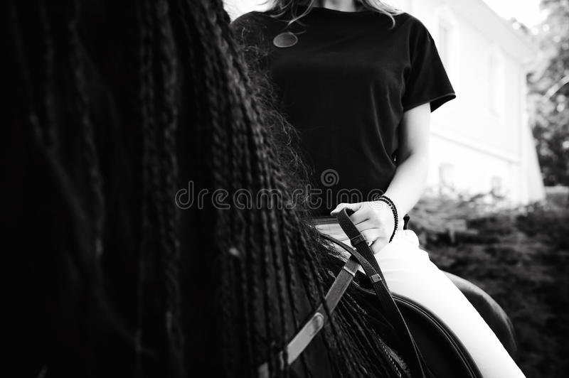 Emotional Portrait of a female in love with horses, black Friesian stallion thoroughbred pet. Emotional portrait of a horsewoman rider woman, astride, in love stock photos