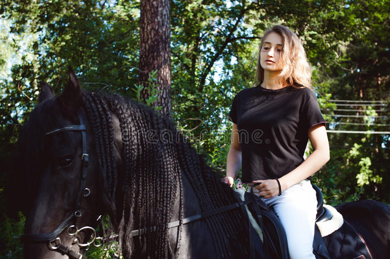 Emotional Portrait of a female in love with horses, black Friesian stallion thoroughbred pet. Emotional portrait of a horsewoman rider woman, astride, in love stock photography
