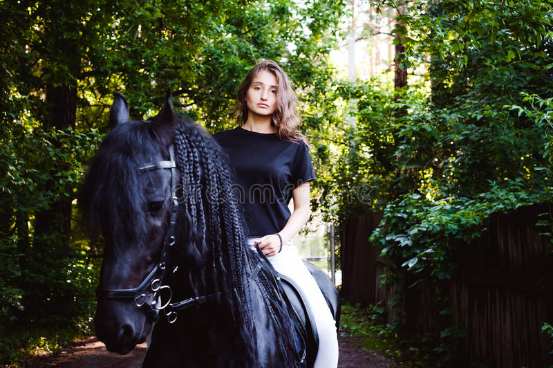Emotional Portrait of a female in love with horses, black Friesian stallion thoroughbred pet. Emotional portrait of a horsewoman rider woman, astride, in love royalty free stock photos