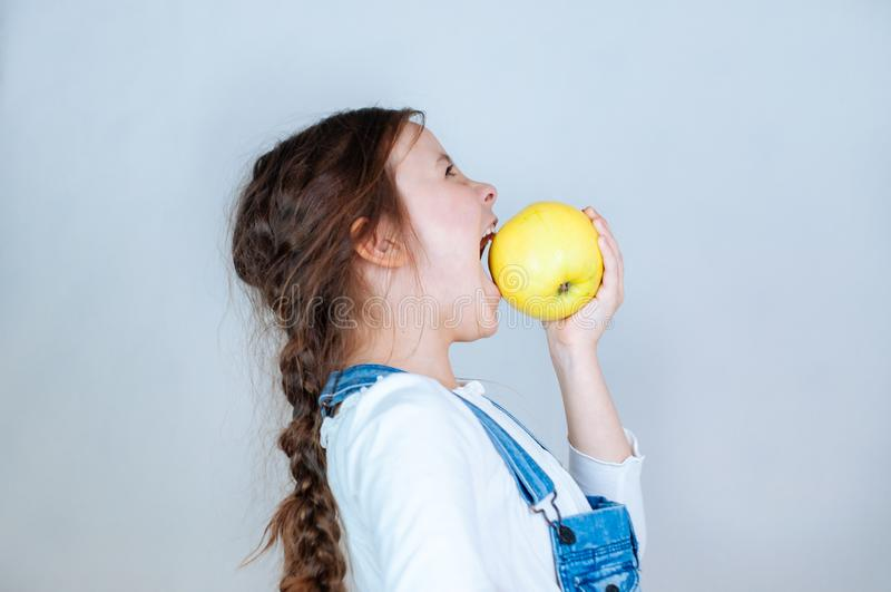 Emotional portrait little beautiful girl with pigtails in jeans overalls eating bites holding an apple. 6-7 years studio stock photos