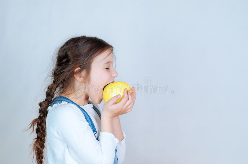 Emotional portrait little beautiful girl with pigtails in jeans overalls eating bites holding an apple. 6-7 years studio stock images