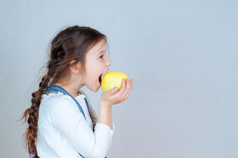 Emotional portrait little beautiful girl with pigtails in jeans overalls eating bites holding an apple. 6-7 years studio royalty free stock photography