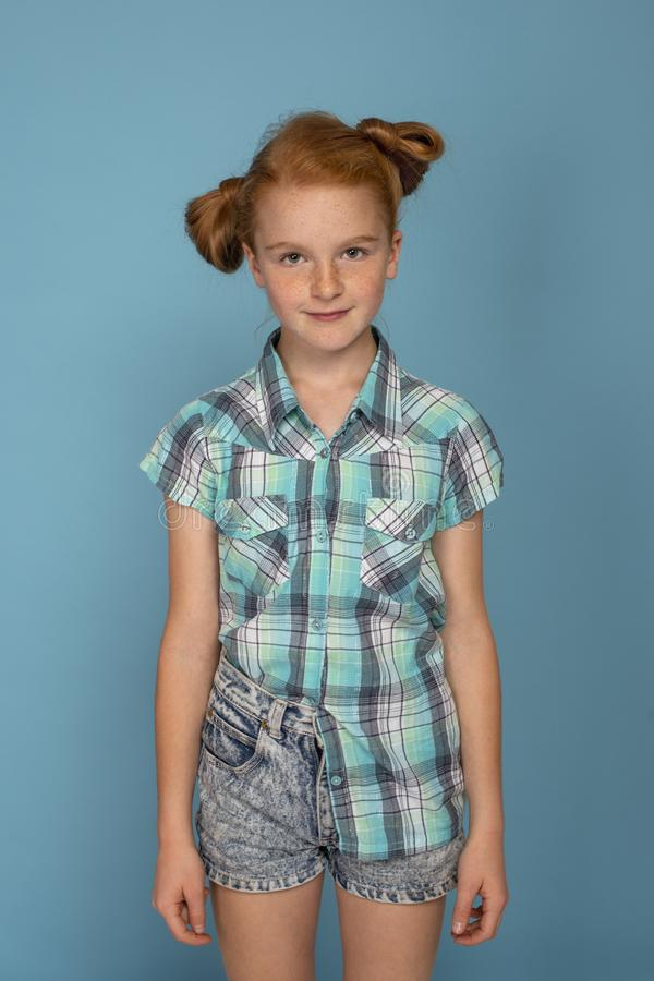 Emotional portrait of a little funny naughty girl with red hair  against  blue background stock photo