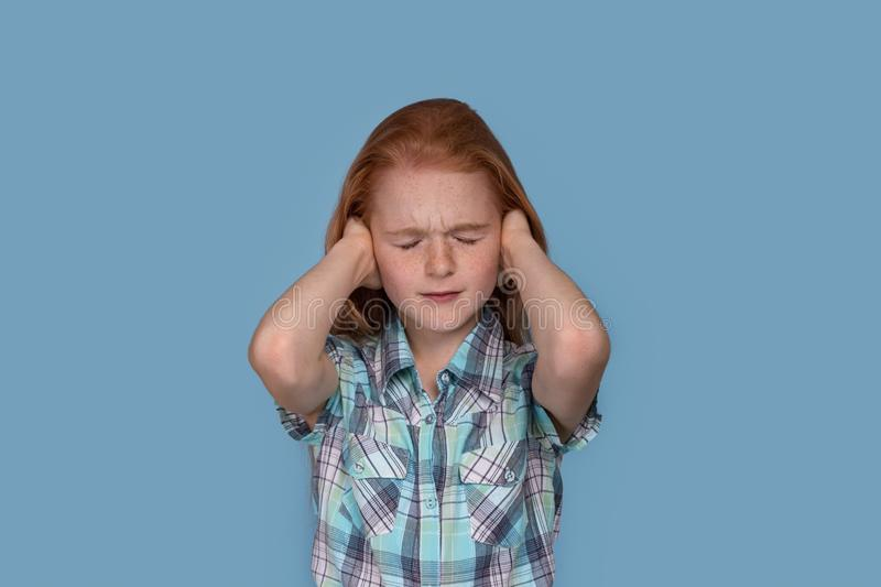 Emotional portrait of a little  girl experiencing stress and holding his head in frustration  against  blue background. Half length emotional portrait of a royalty free stock photography