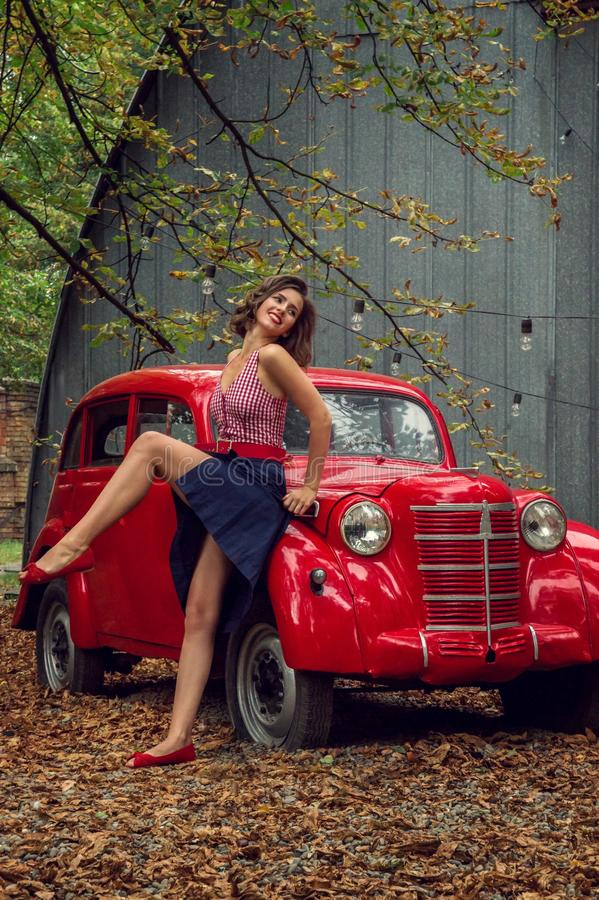 Emotional portrait. Pin-up girl posing near by a red russian retro car.The model laughs loudly, flirtatiously showing slender legs.  royalty free stock photos